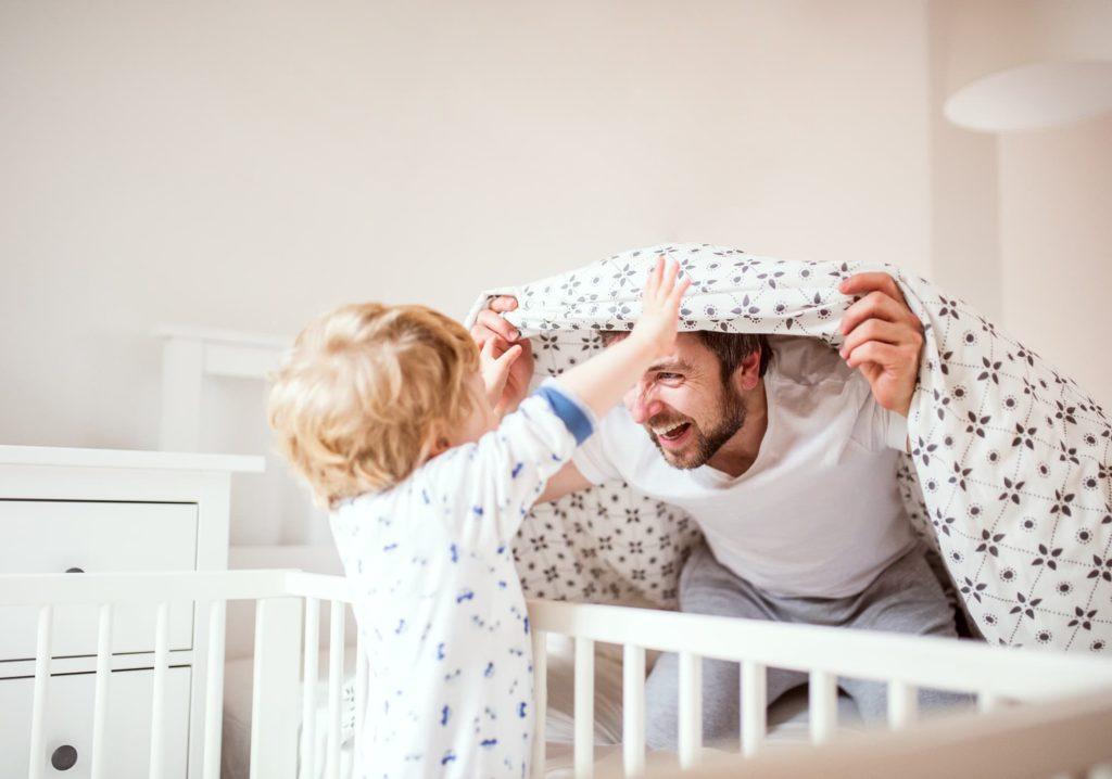 Vater und Sohn spielen vor dem Einschlafen. Das Kind steht im Kinderbett auf einer Ehrenkind Babymatratze