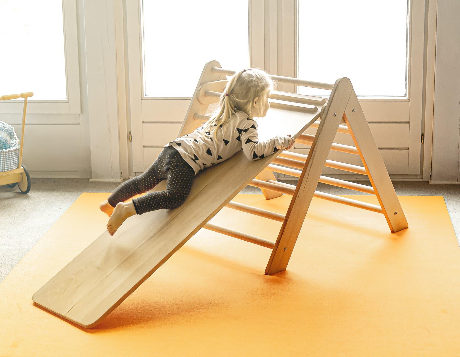 Mädchen spielt auf dem Kletterdreieck