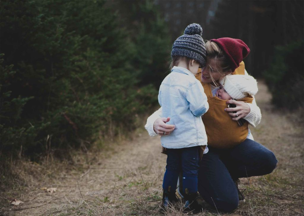 Mutter mit Baby und Kleinkind im Wald