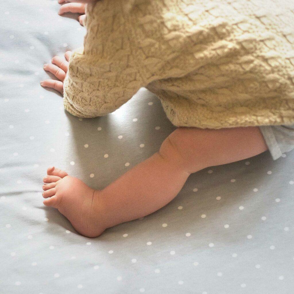 Graue Krabbeldecke mit weißen Punkten mit Baby